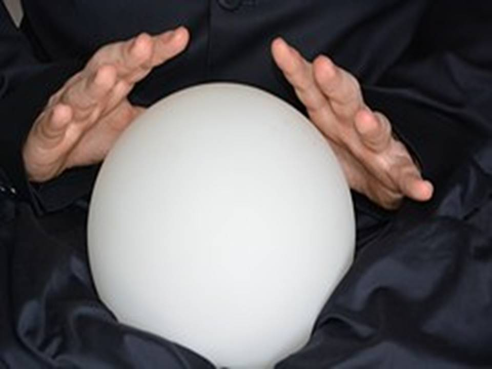 white crystal ball with hands over it